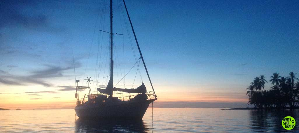 sailboat karl at anchor in guna yala with palm tree island and beautiful sunset