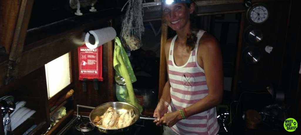 sailor girl cooking fish in sailboat galley