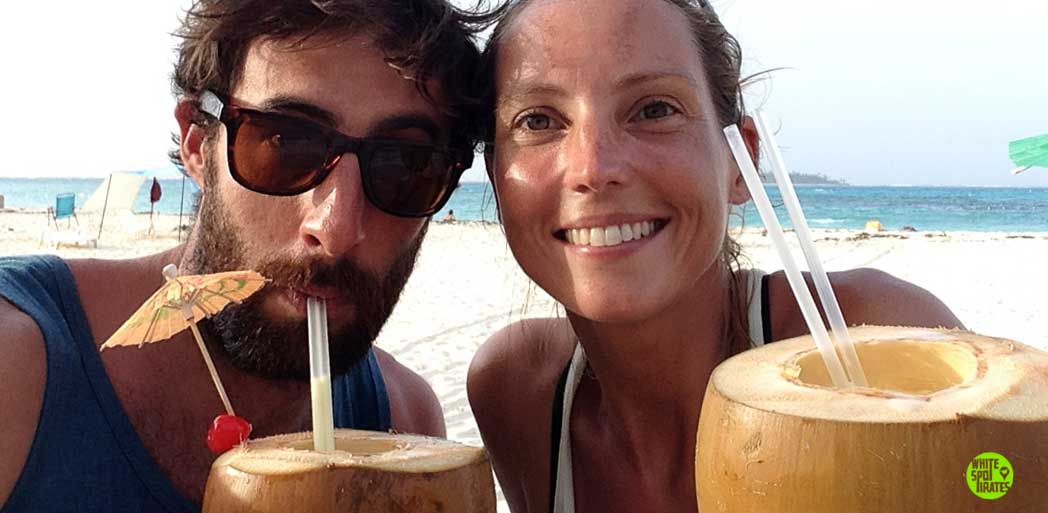 couple on a beach with two coconut cocktails
