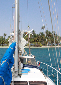 sailboat Karl in front of palm tree island in San Blas