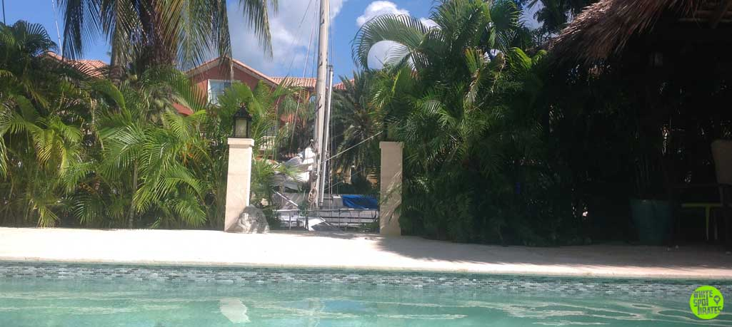 sailboat karl at a dock of a house with a pool in cayman island
