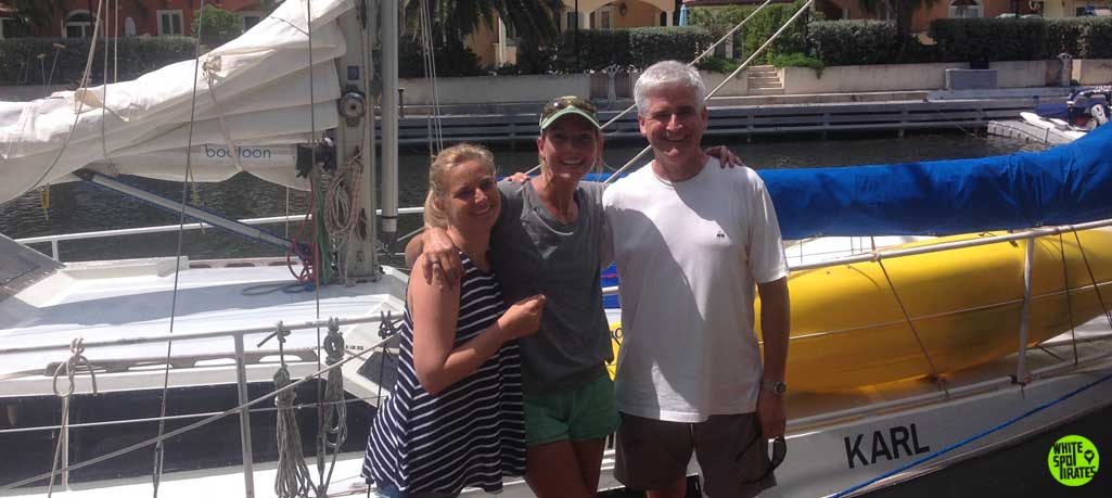 three people and sailboat karl on a dock in cayman island