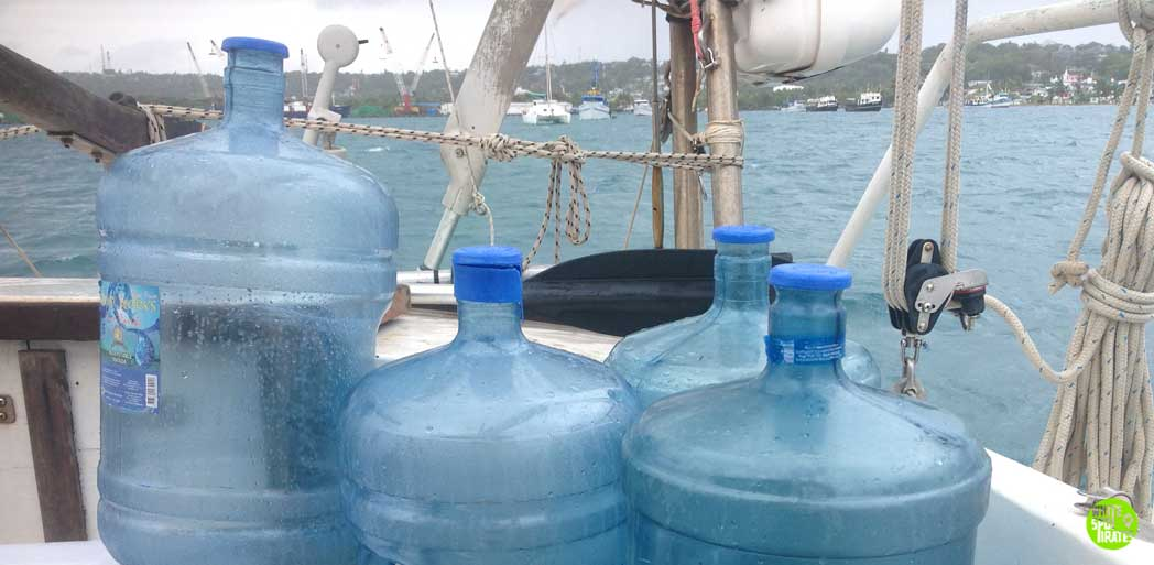 four empty water jugs on a sailboat