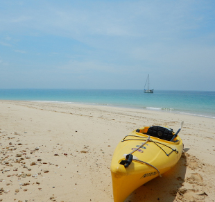 Kayak on white beach in Belize with a sailboat